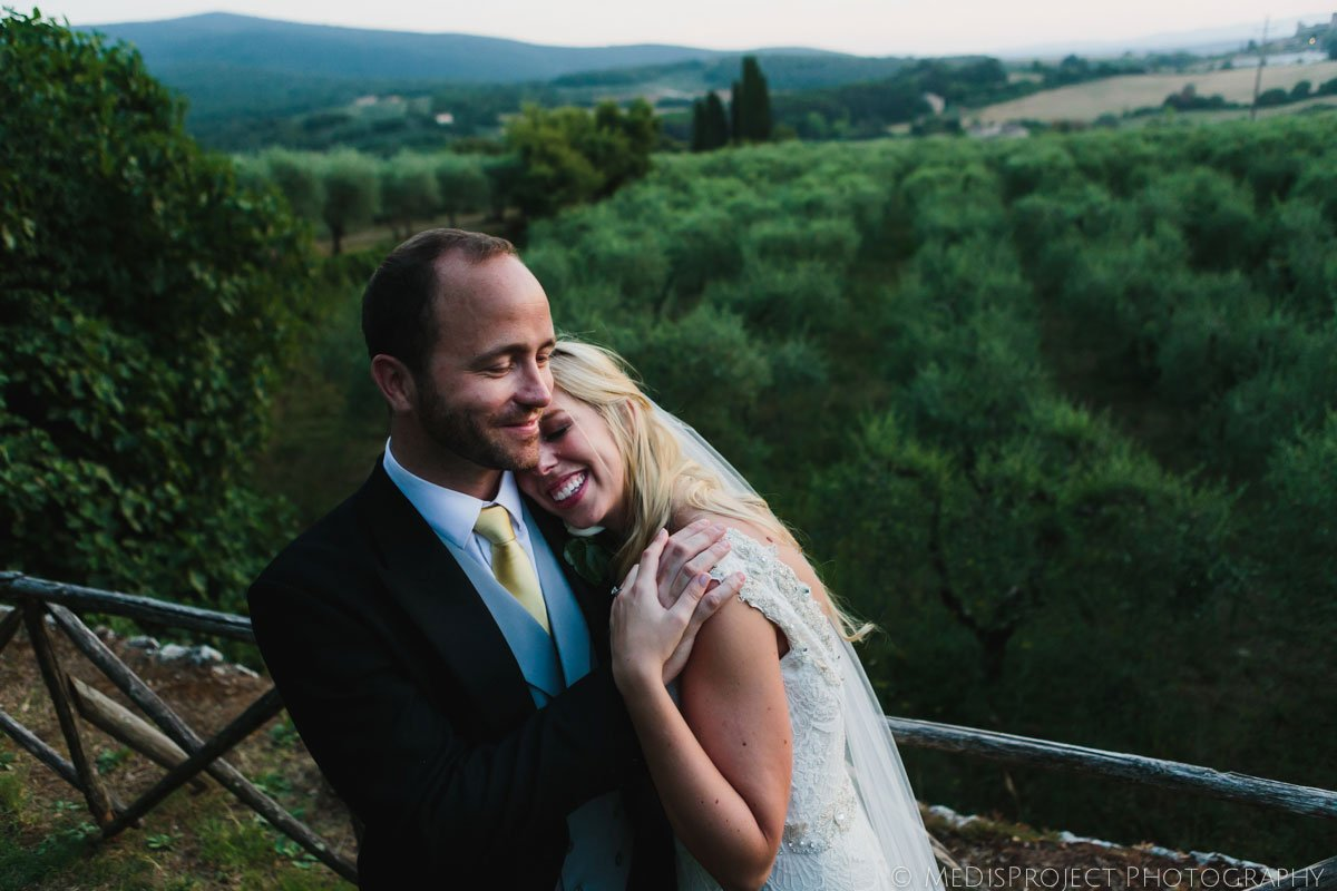 bride and groom hugging surrounded by olive trees in dusk golden light