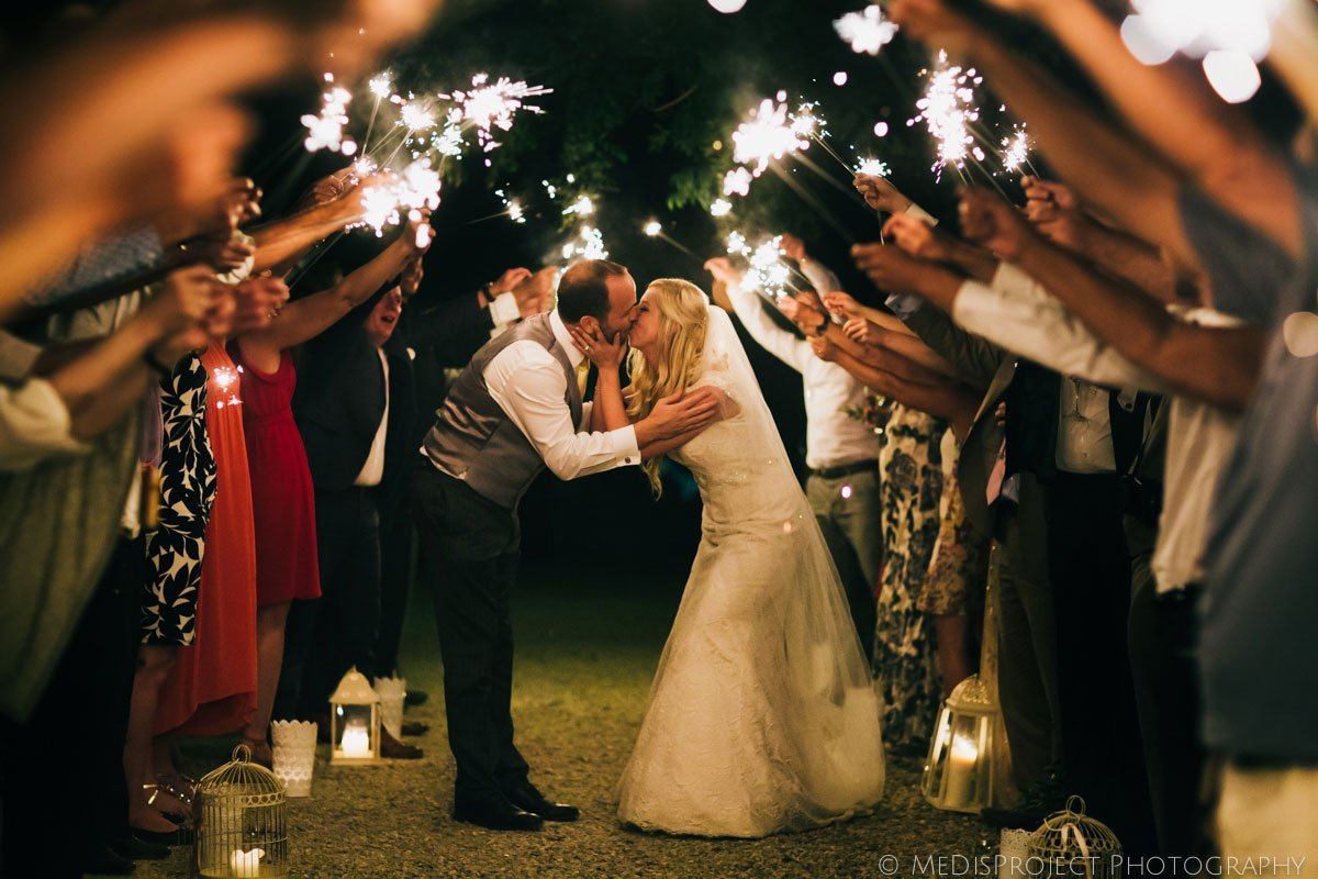 Bride and groom kissing under a sparklers tunnel