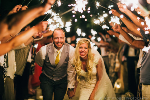 Bride and groom walking under a sparklers tunnel