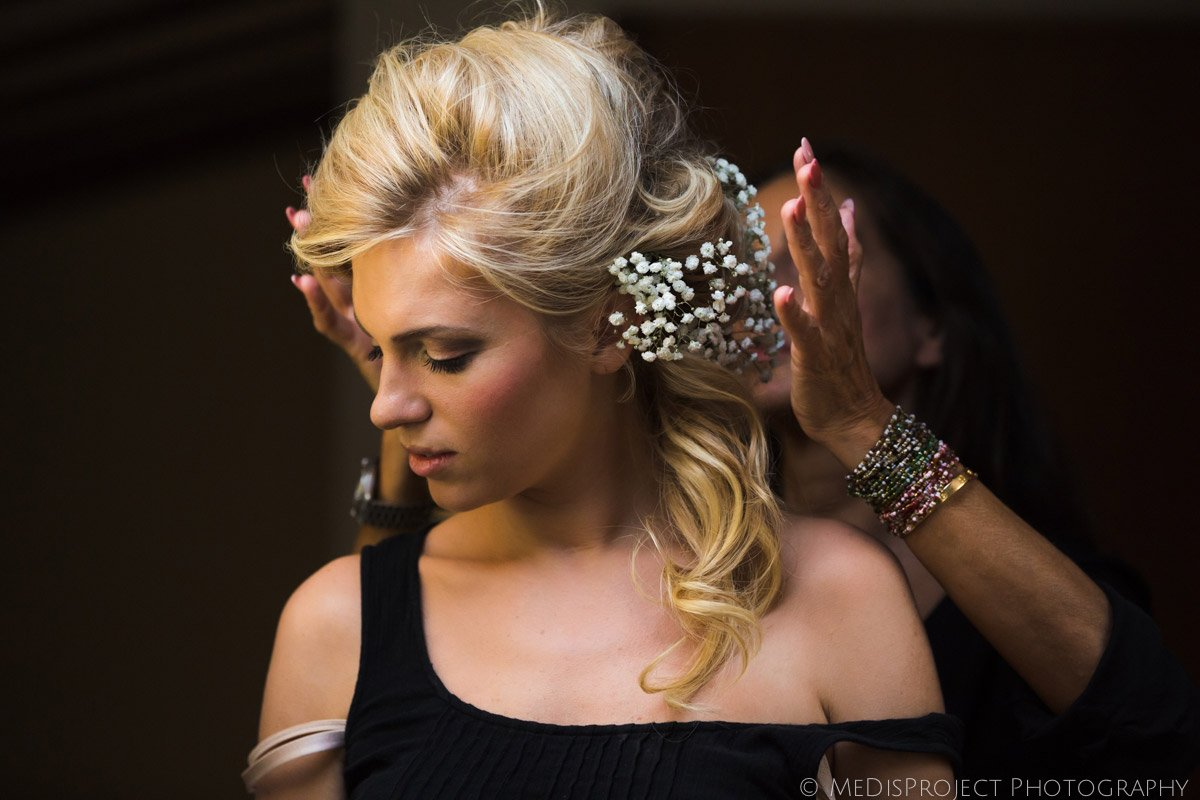 beautiful blonde bride with the hairdresser before the wedding ceremony