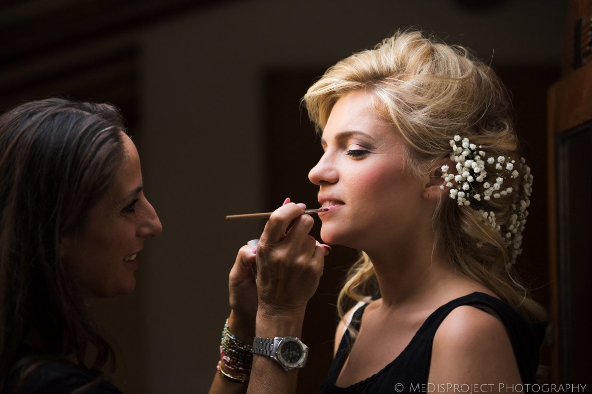 beautiful blonde bride doing make up before the wedding ceremony