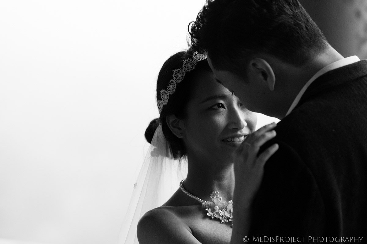 black and white photo of a bride facing her groom in a foggy day