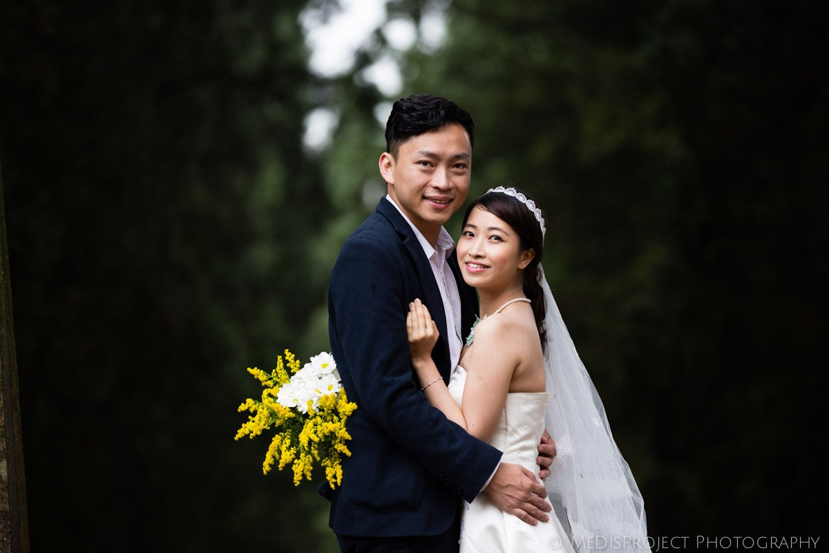 Chinese bride and groom standing in the middle of a cypress boulevard in Villa Agape