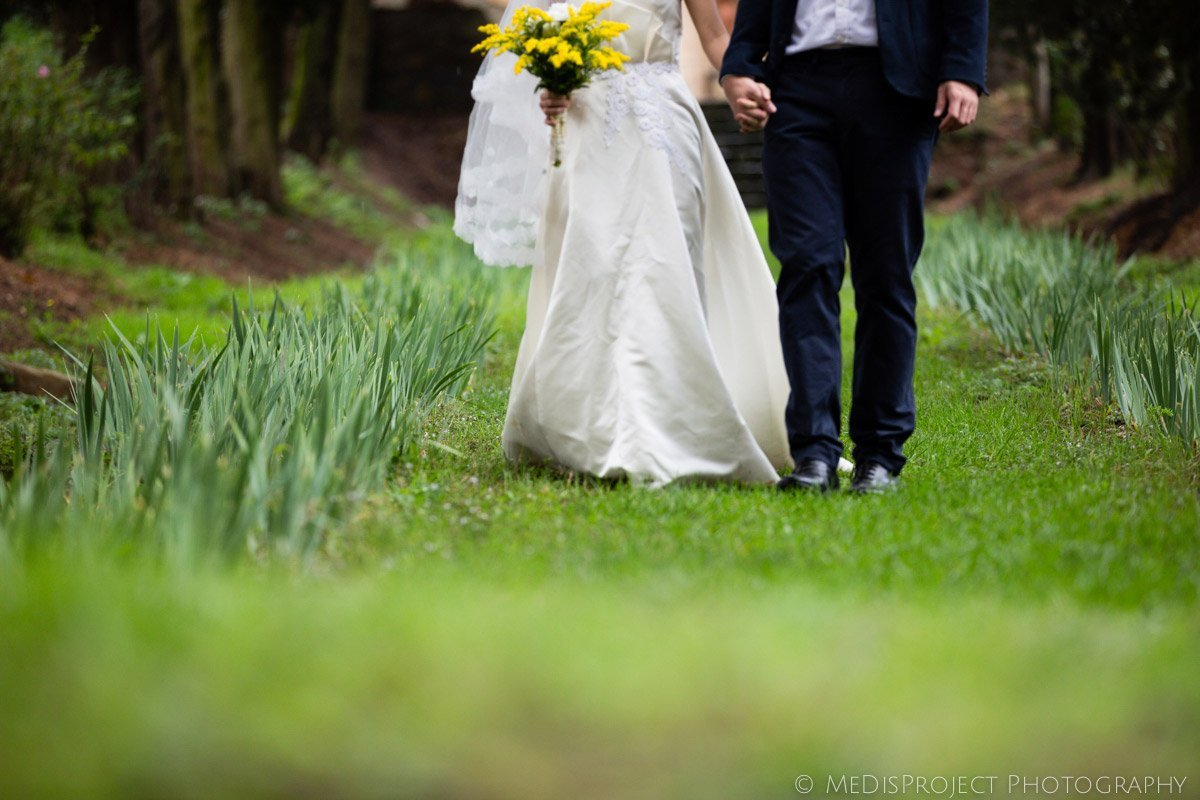 detail of a bride and groom walking through a cypress boulevard in Villa Agape