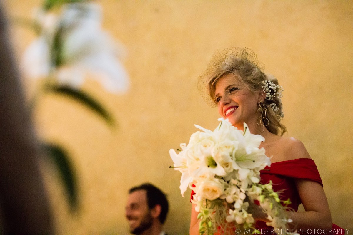 beautiful blonde bride with white bouquet during wedding ceremony