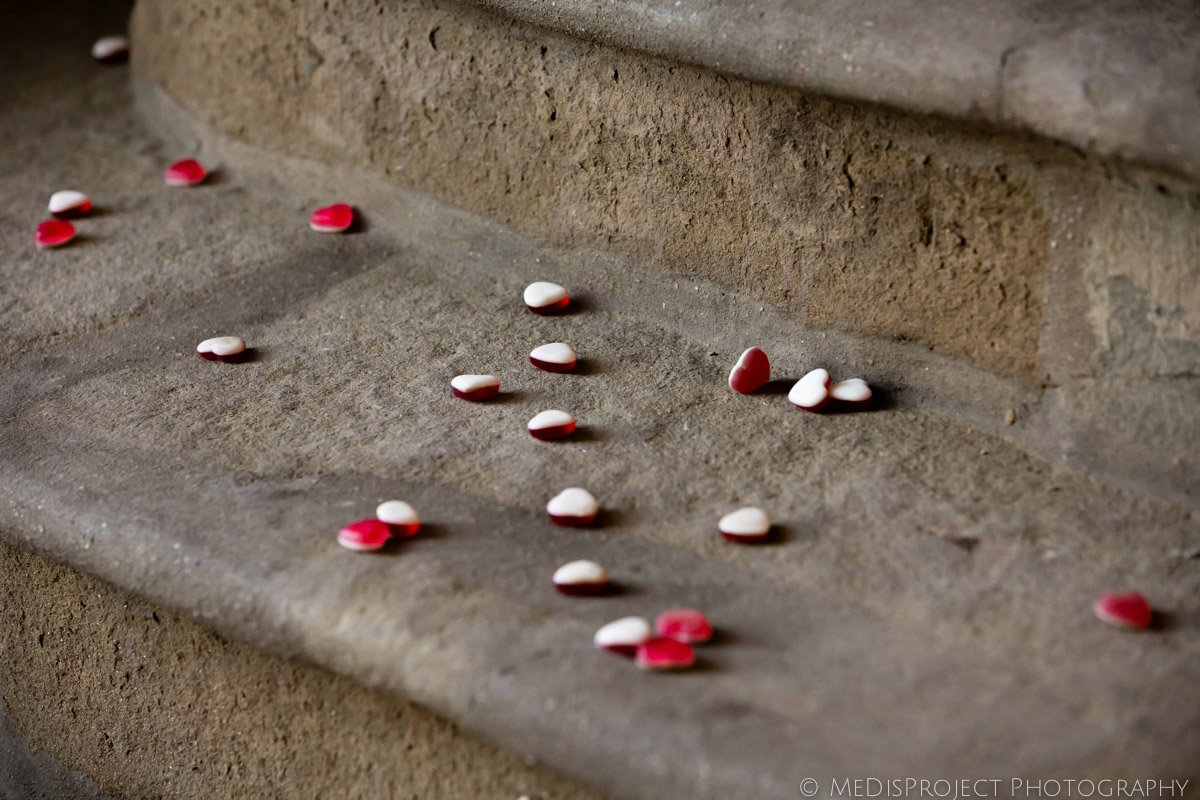 red and white gummy hearts confetti thrown to a just married couple