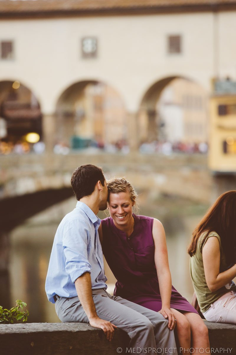 young engaged couple kissing next to Ponte vecchio in Florence