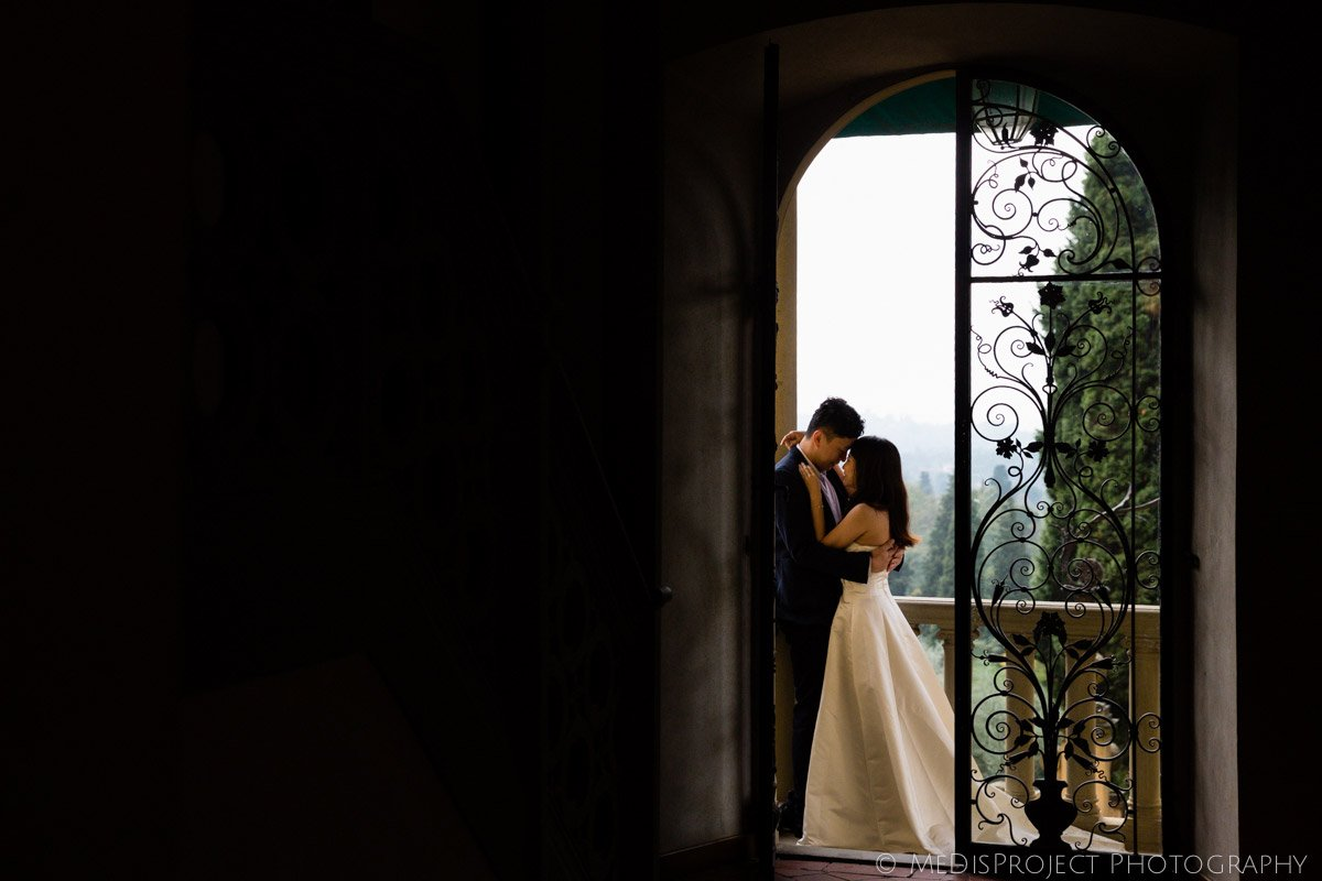 couple facing each other on wrought iron doorway in Villa Agape