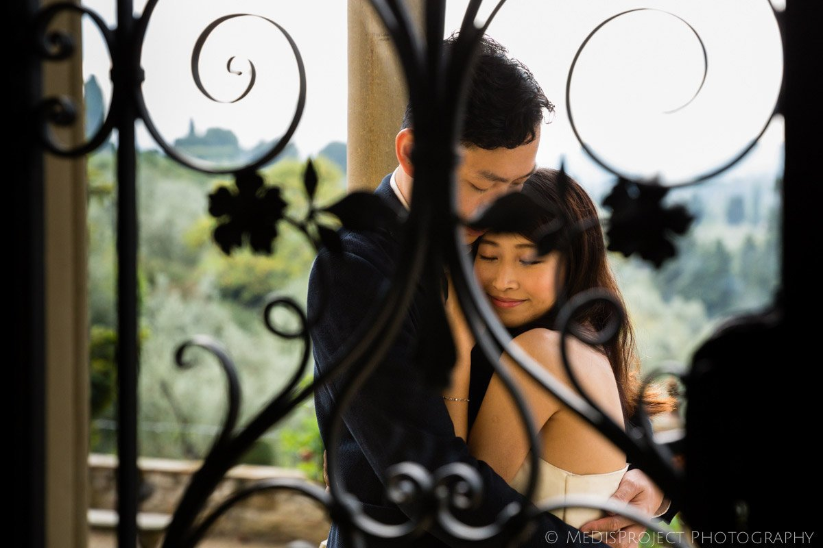 oriental couple hugging seen through a wrought iron window in Villa Agape