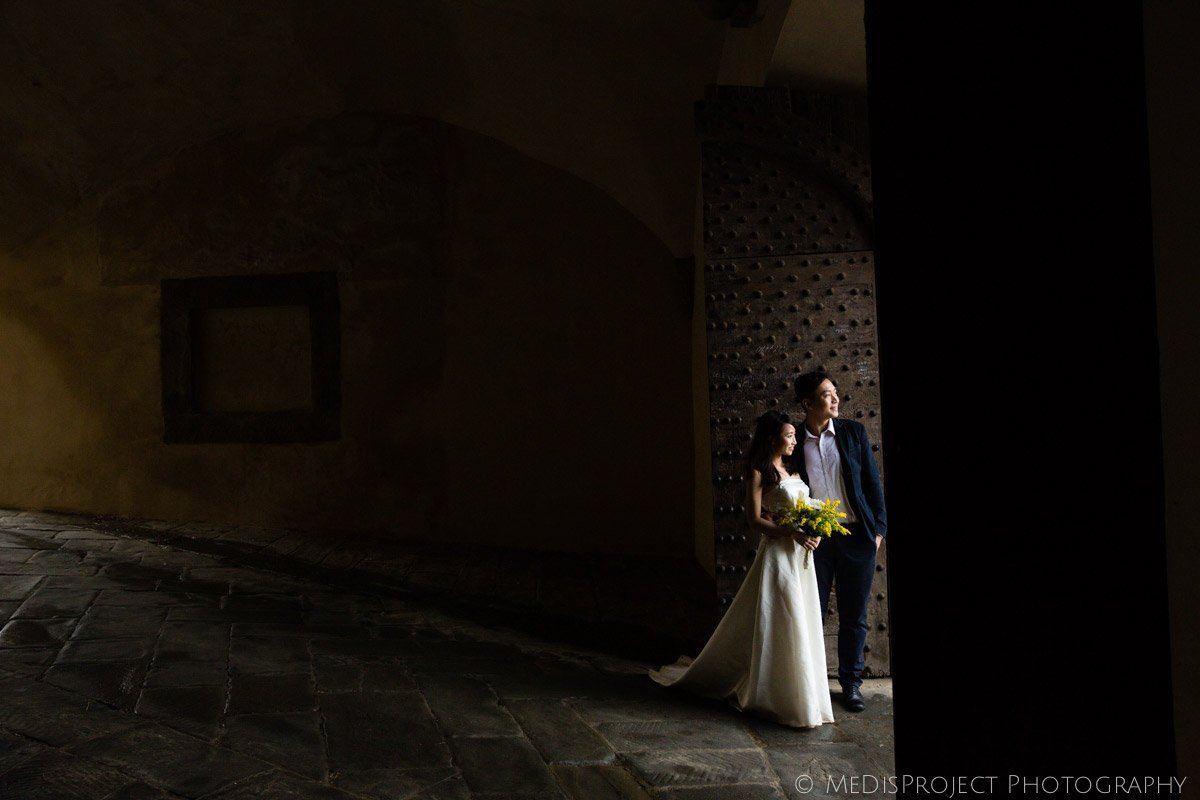 oriental couple standing on a monumental wooden doorway in Florence