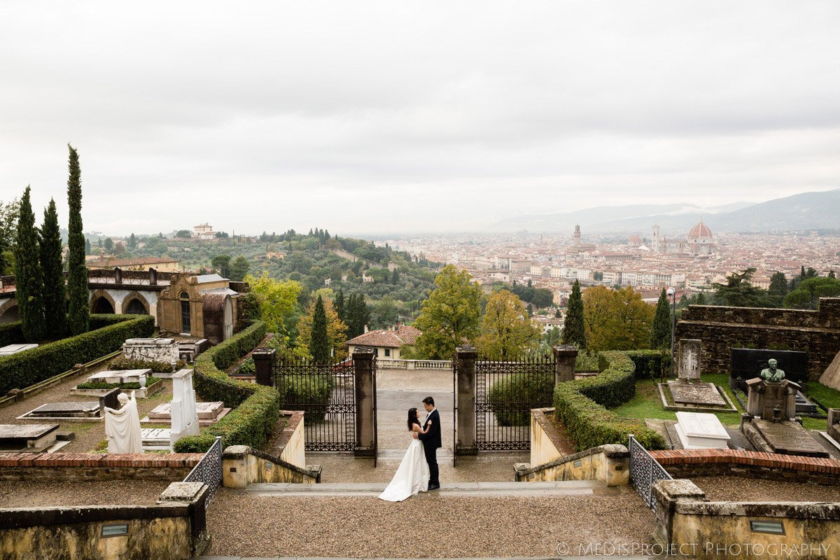 Happy couple standing in the middle of San Miniato church stairway in Florence