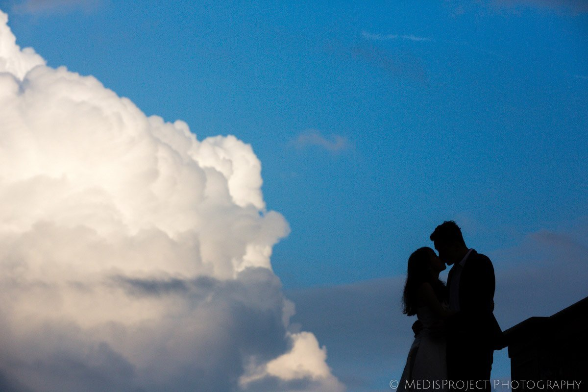 silhouette of a couple kissing under a blue sky with white foamy clouds