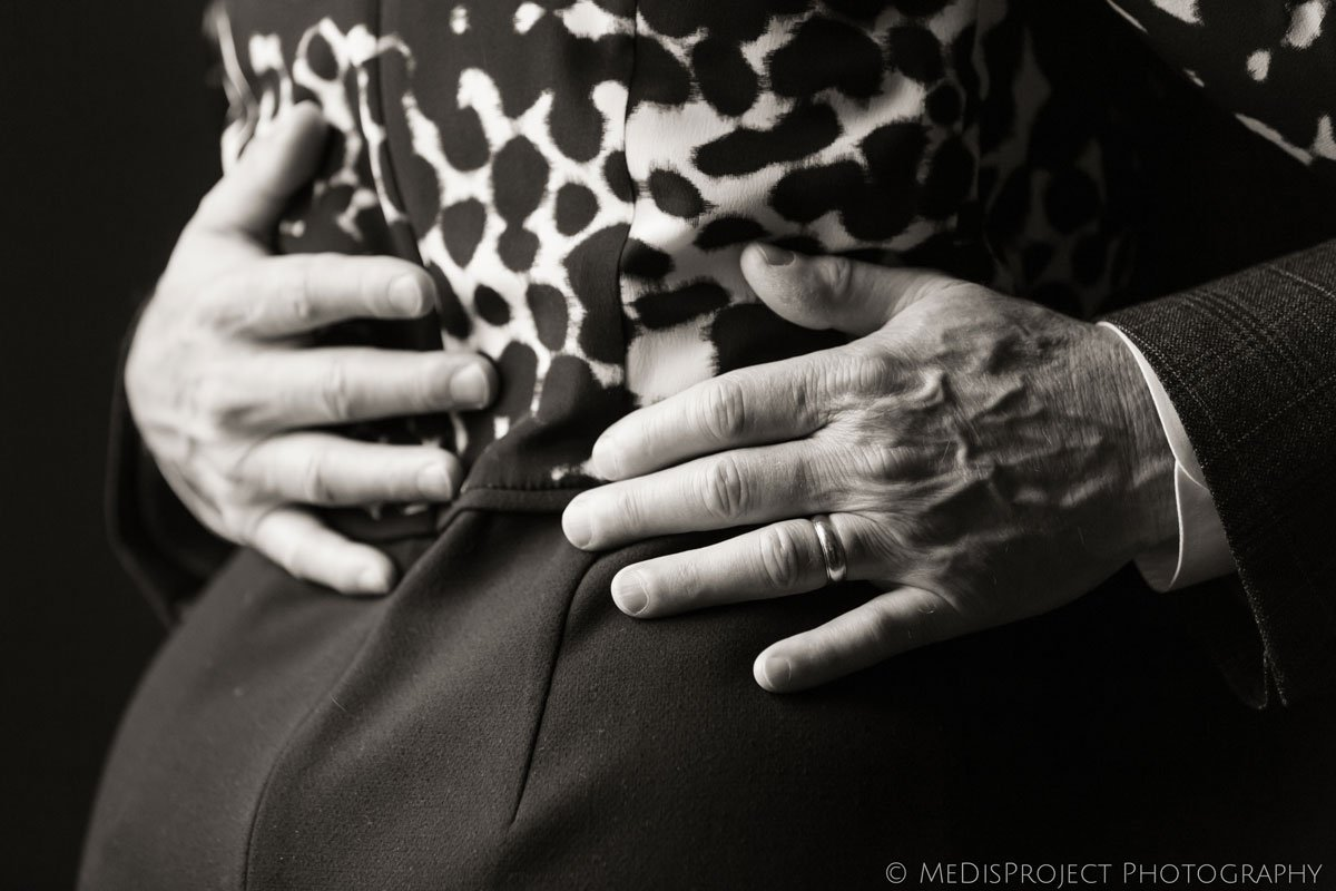 Black and white old man hands holding a woman