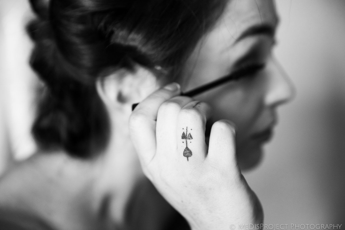 black and white picture of the bride putting mascara on before the ceremony