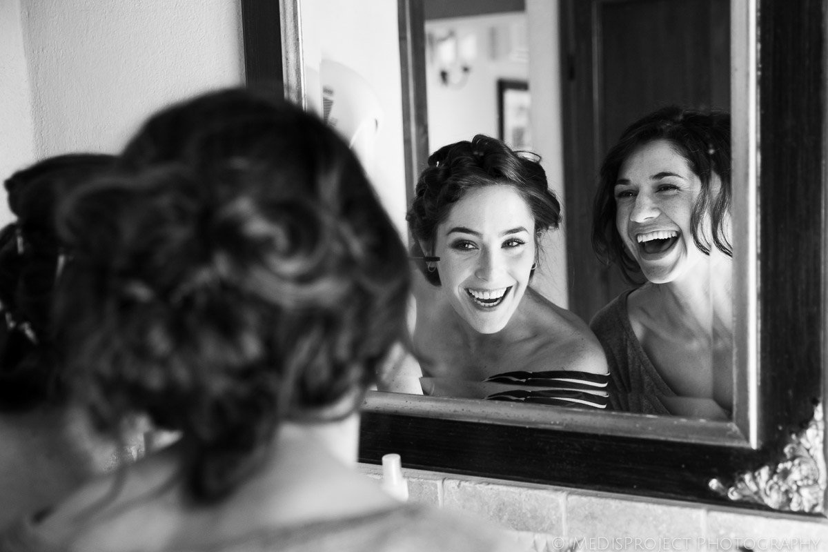 black and white picture of the bride having fun with her bridesmaid at the mirror while getting ready