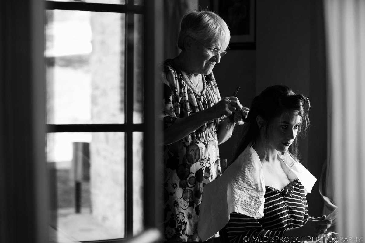 black and white picture of the bride hairdressing before the ceremony