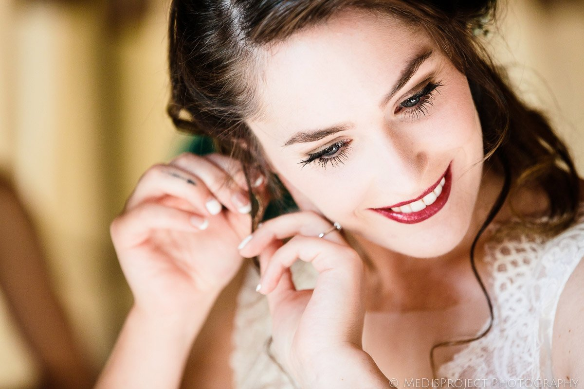 stunning brunette bride putting earrings on just before the wedding ceremony