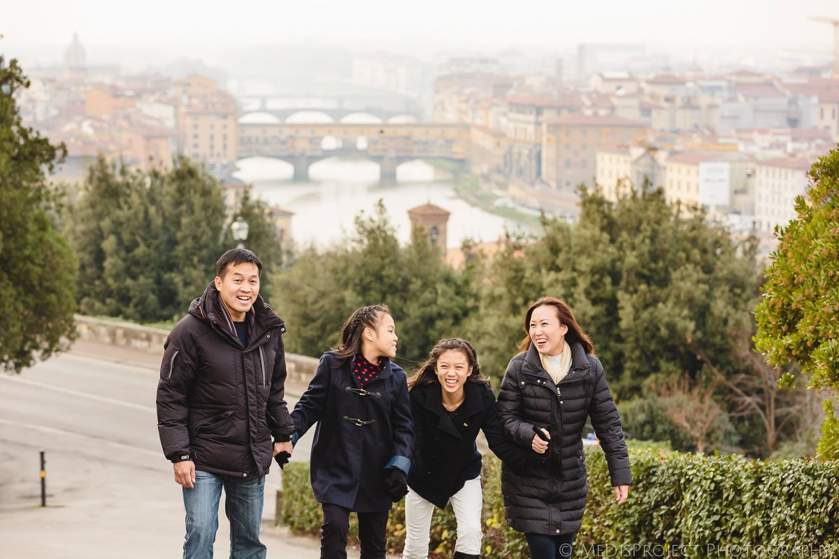 Family portrait of four walking side by side in Florence