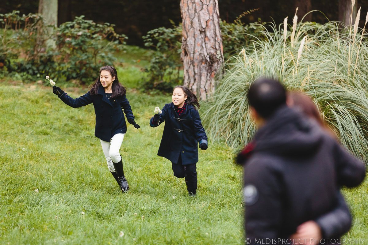 oriental girl running in a field with parents watching them