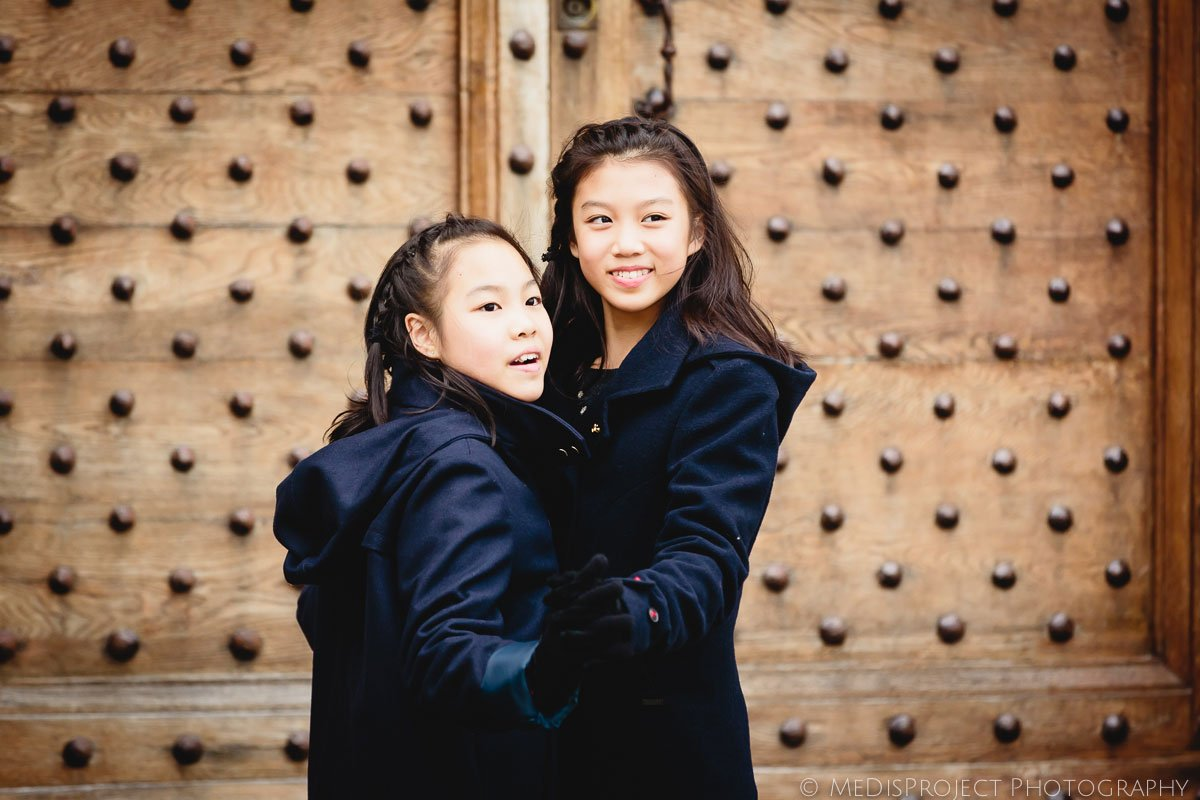 sisters portrait in front of an old wooden door