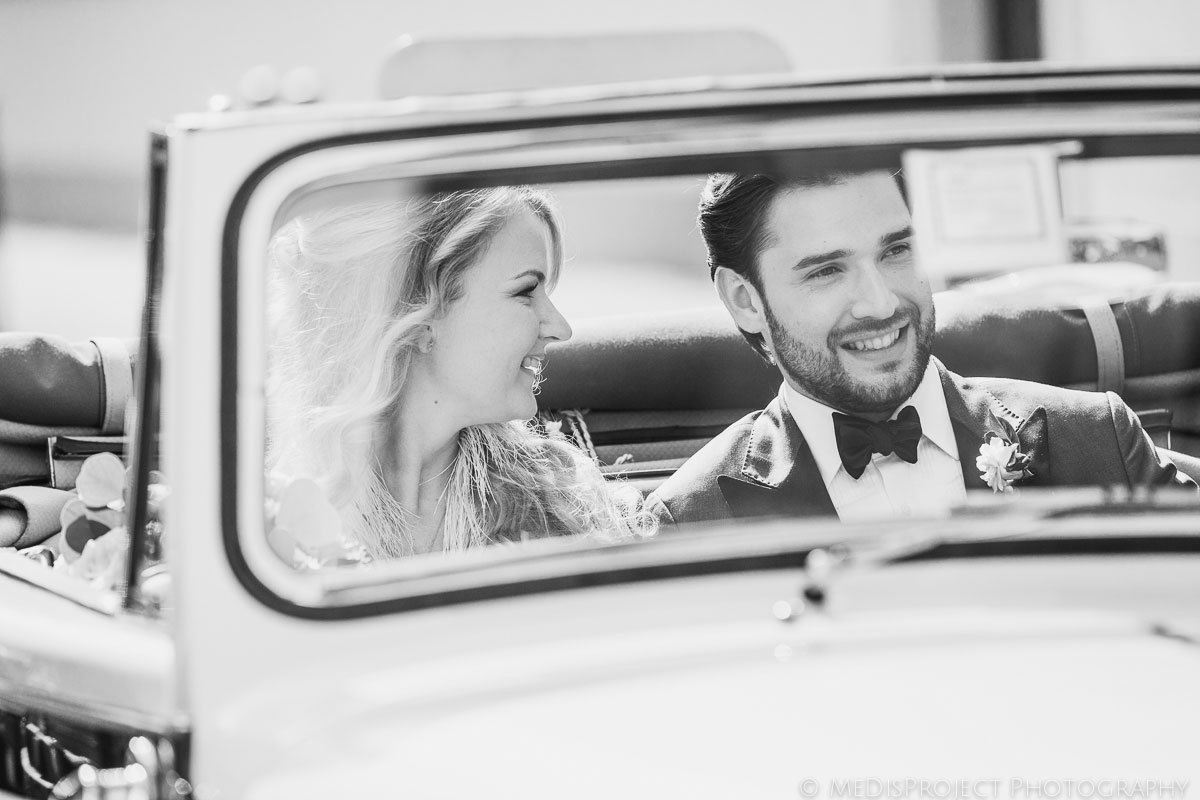 bride and groom on elegant wedding car