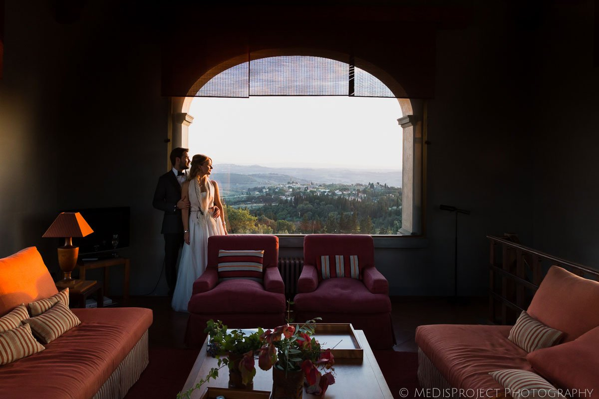 bride and groom staring at sunset from the top of Villa Tavernaccia