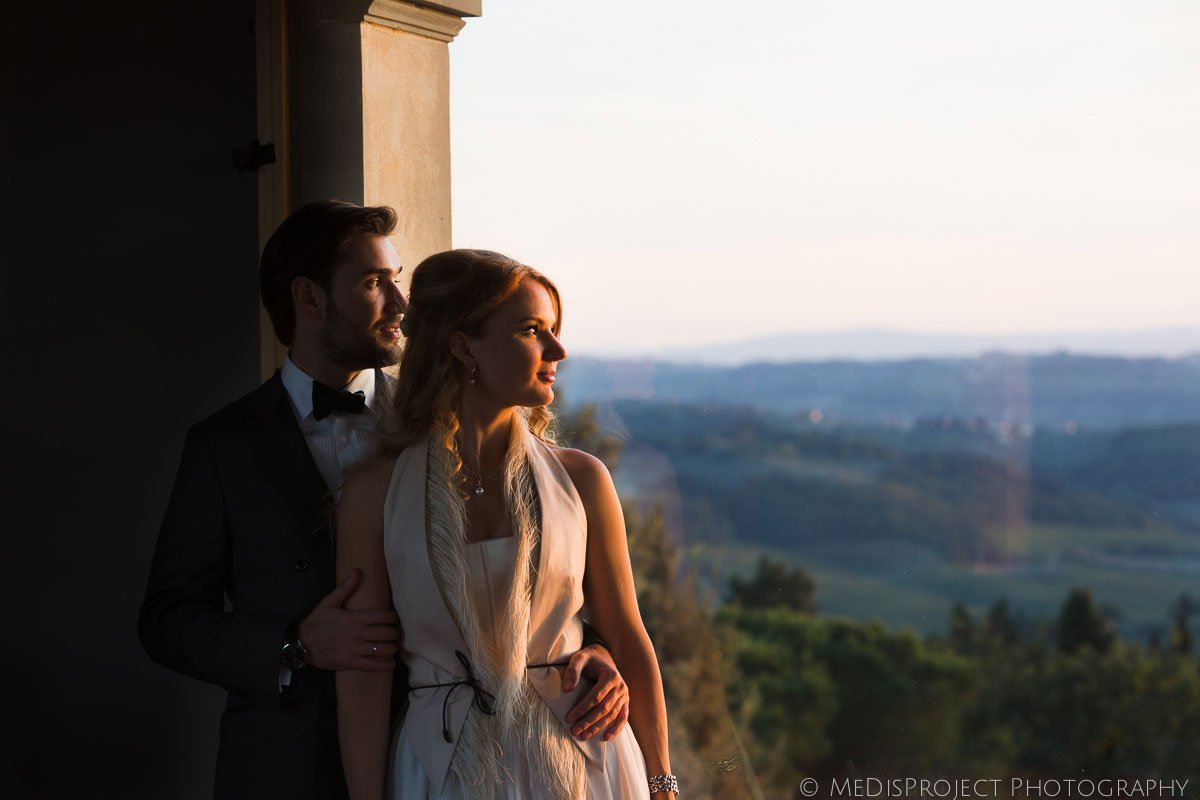 bride and groom staring at sunset from Villa Tavernaccia