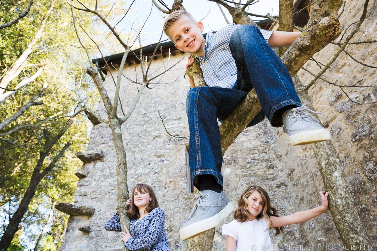 portrait of siblings on a tree in Tuscan countryside