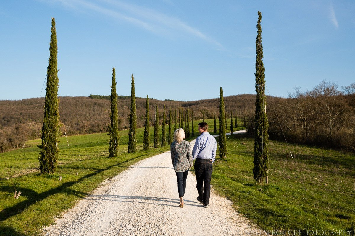 couple walking on a cypress boulevard in Tuscany