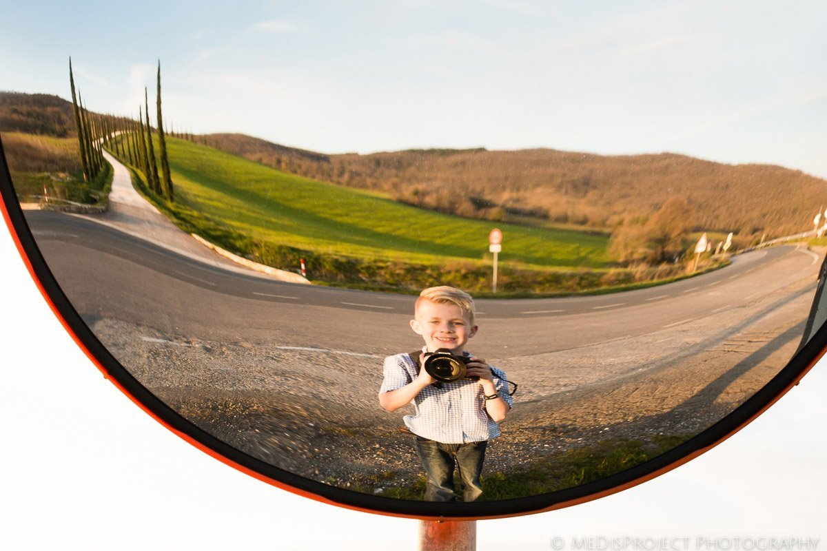 kid taking a selfie at a convex mirror with photographer's camera