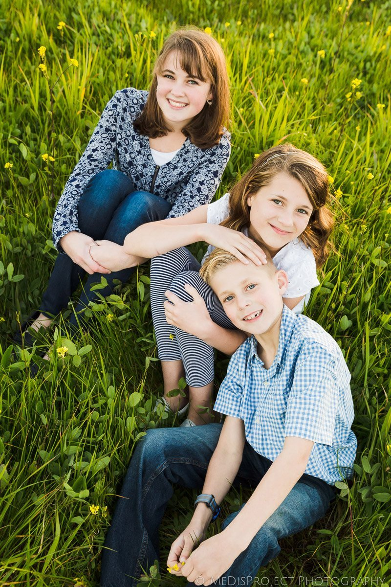 siblings portrait sitting on the grass