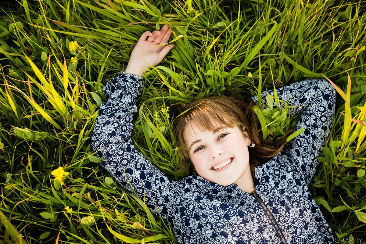 teenager smiling girl laying in the green grass