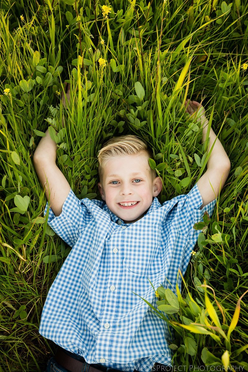 smiling kid laying in the green grass