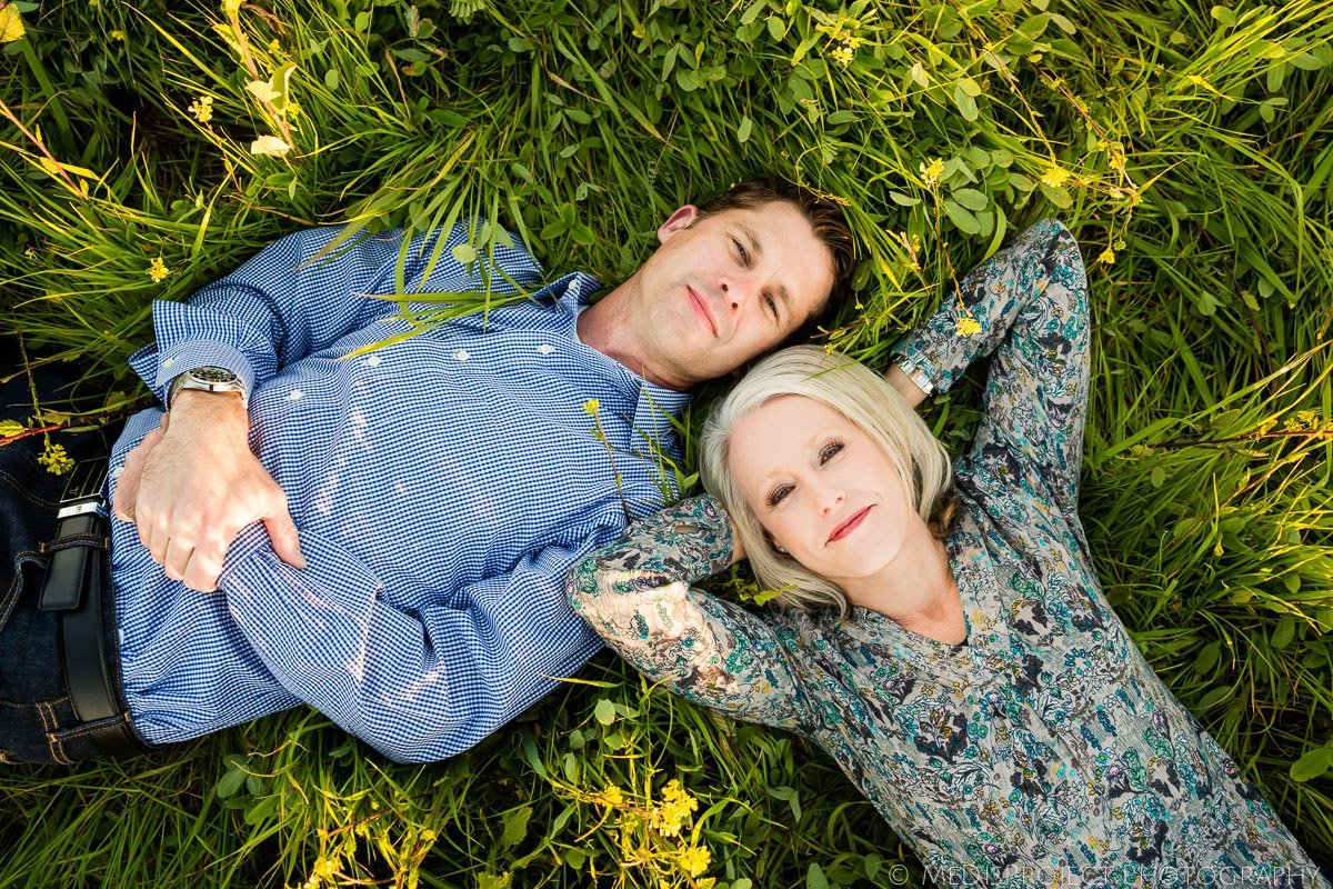 parents laying in the grass during a family photo session in Tuscany