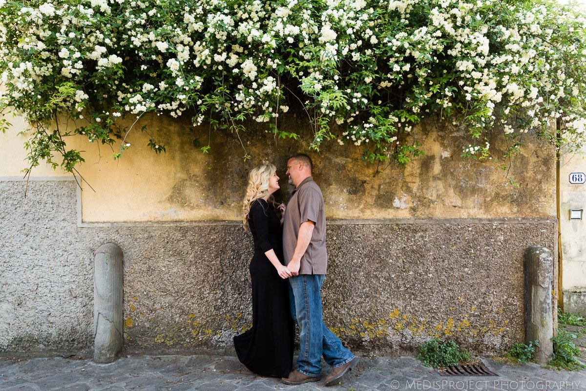 romantic couple standing under a rose tree
