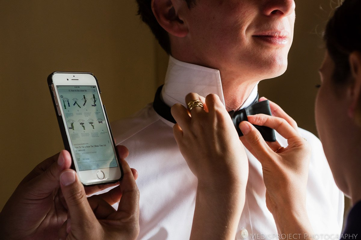 groom and his friends tying his bow tie with a tutorial on mobile phone