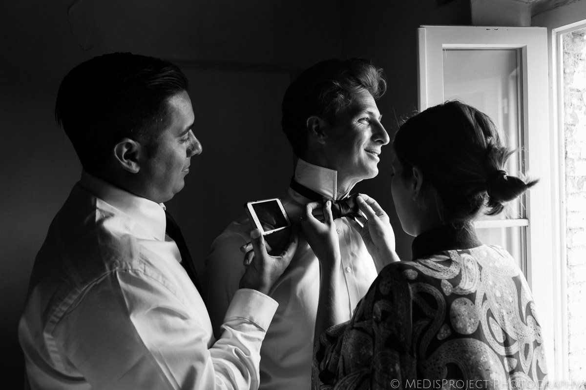 groom and his friends tying his bow tie before the wedding