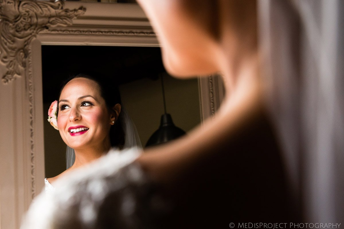 bride smiling at the mirror before wedding ceremony