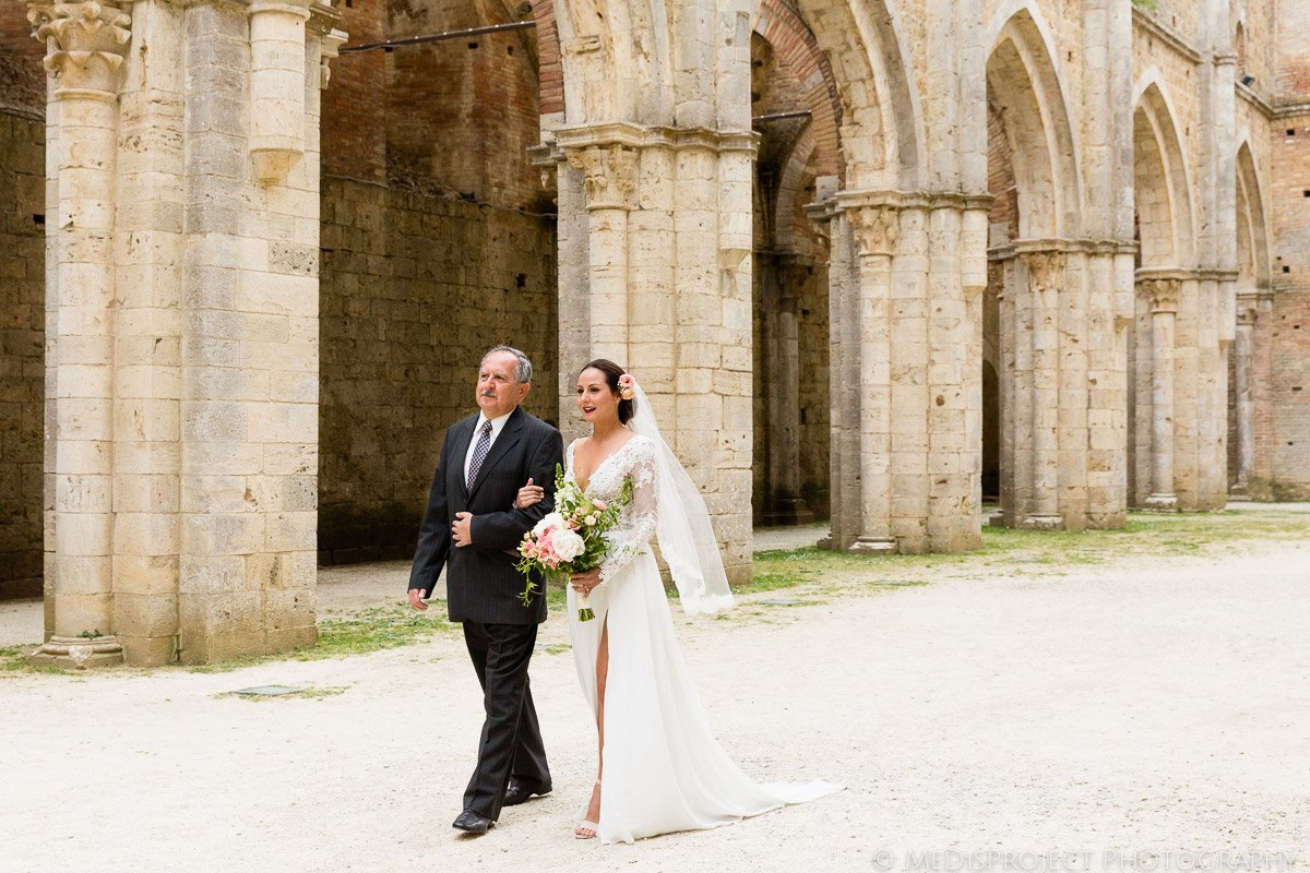 The bride walks down the isle in San Galgano roofless church