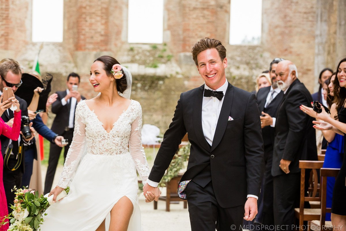 Bride and groom walk the isle after their wedding in San Galgano roofless church