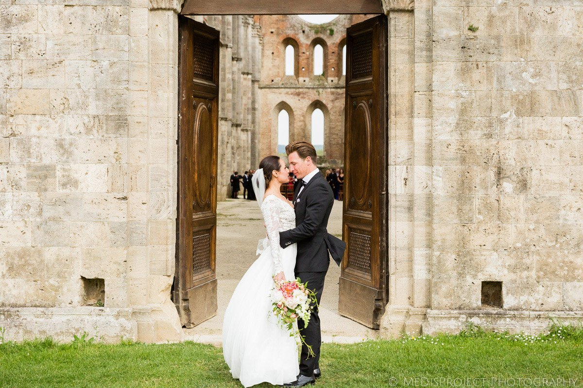 Bride and groom kissing in San Galgano roofless church