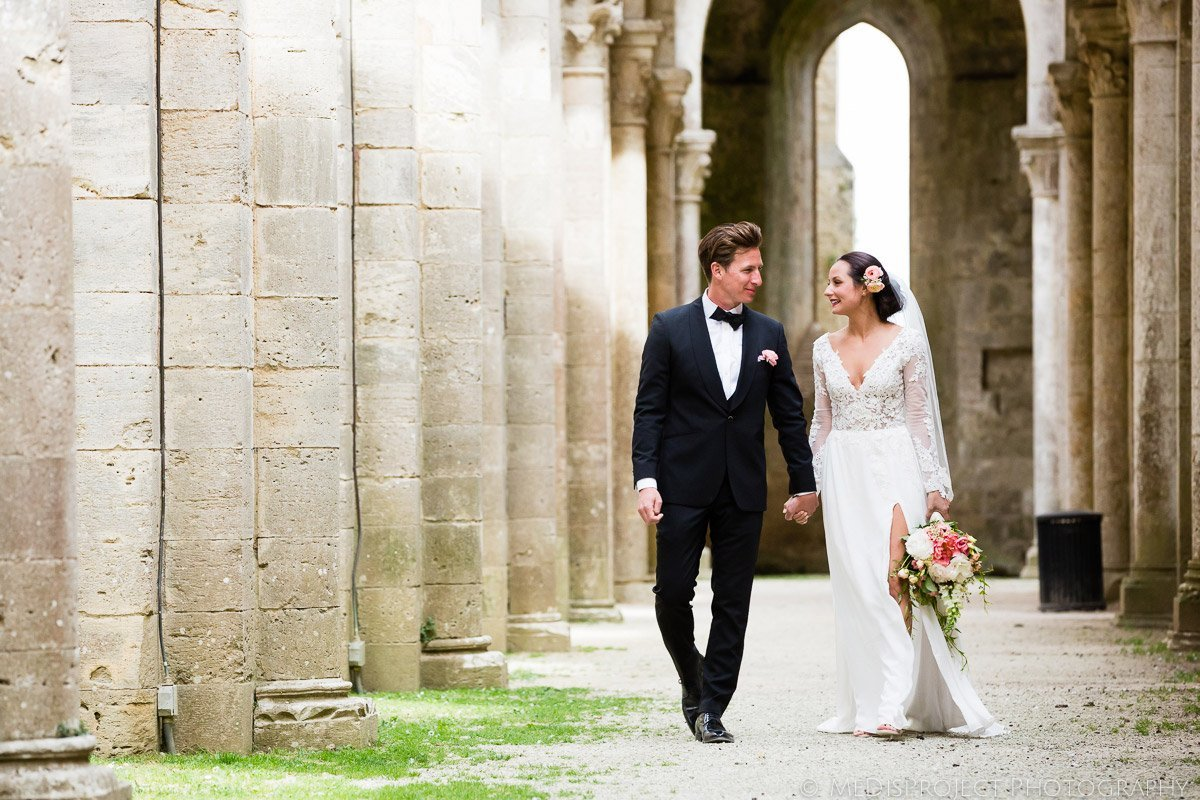 Bride and groom walking in San Galgano roofless church