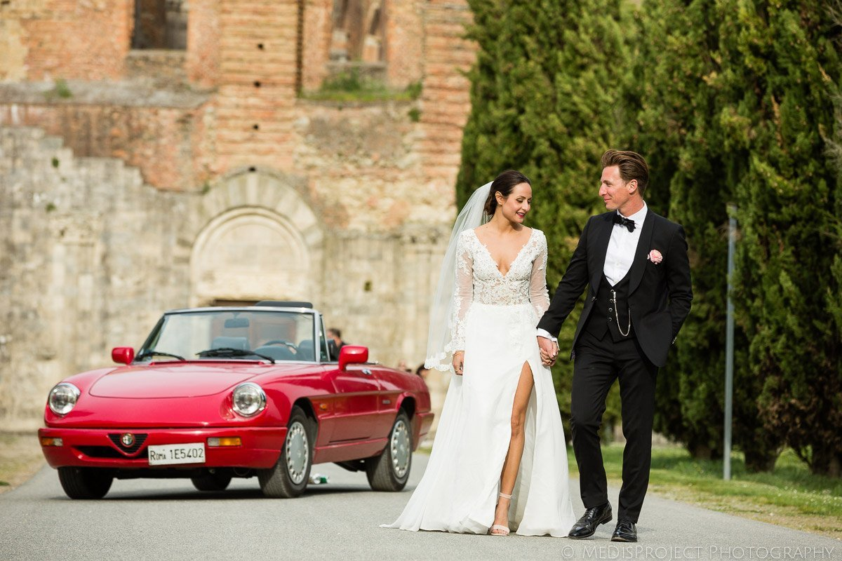 Bride and Groom shooting in San Galgano with red vintage car