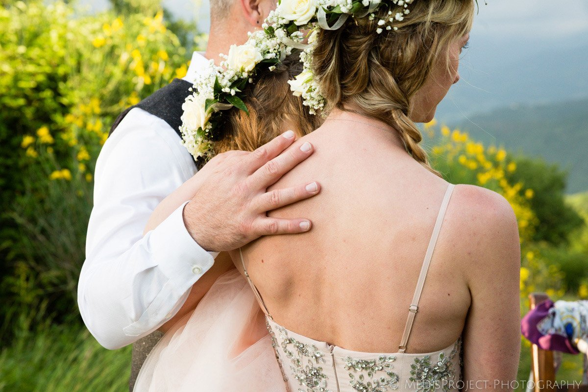 detail of a groom's hand on bride's shoulder during the wedding ceremony