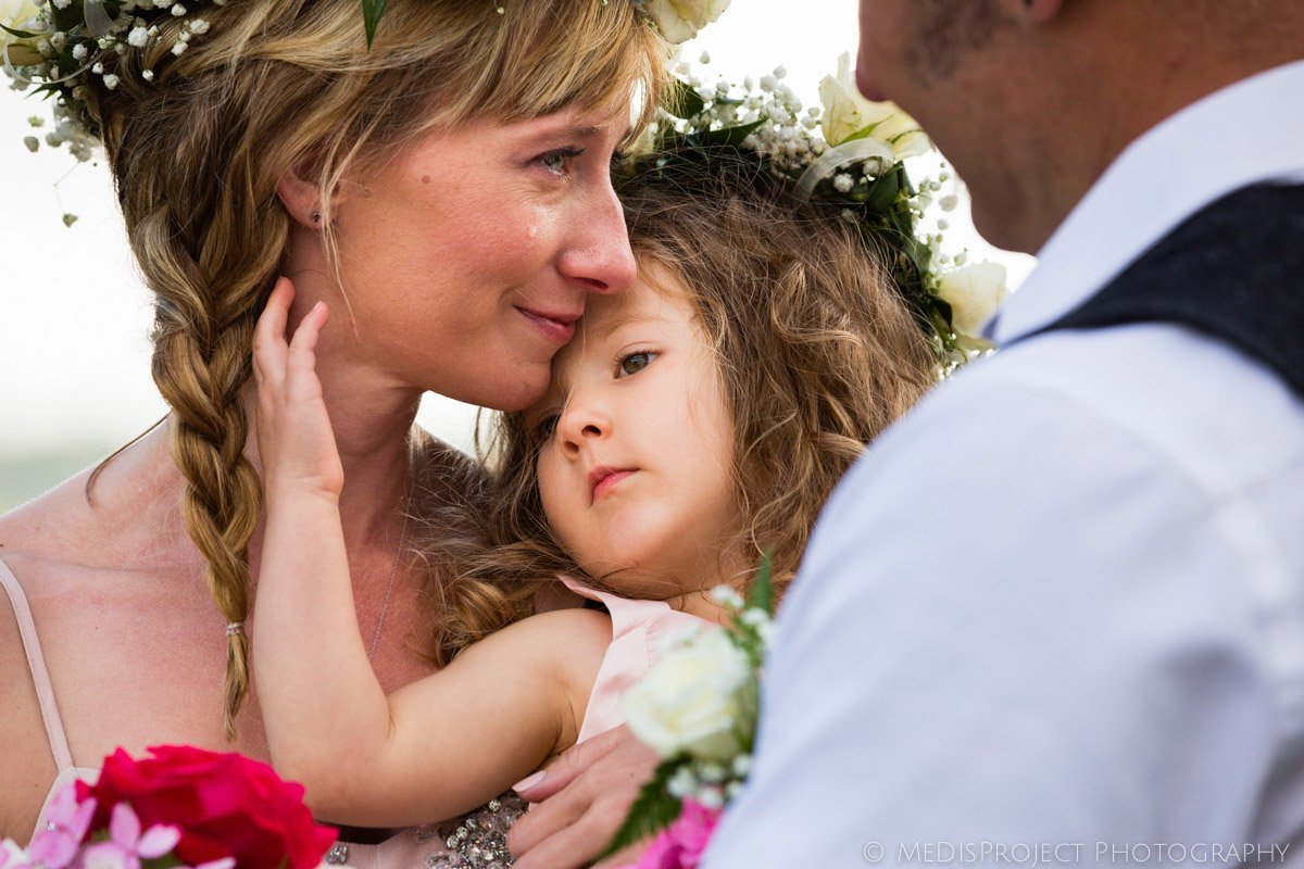 little flower girl comforting her mother during a wedding ceremony