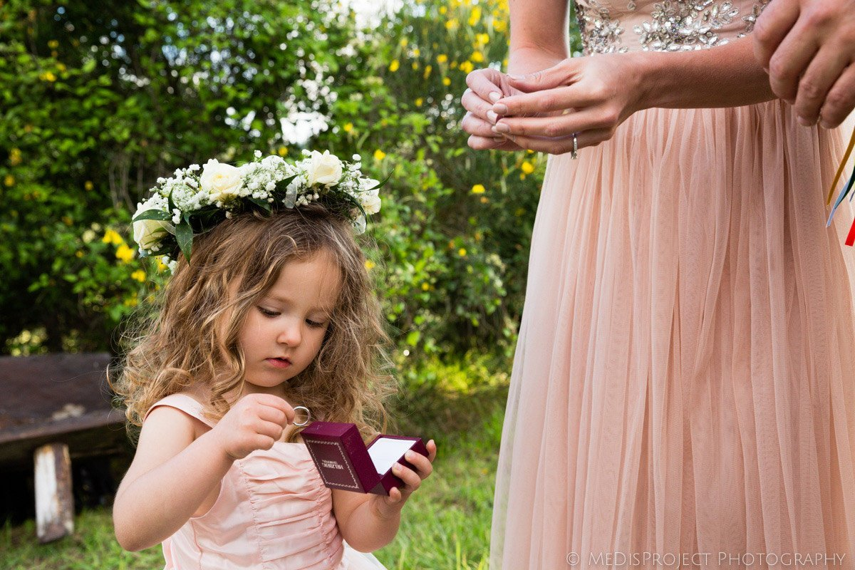 little flower girl bringing the rings to the bride and groom