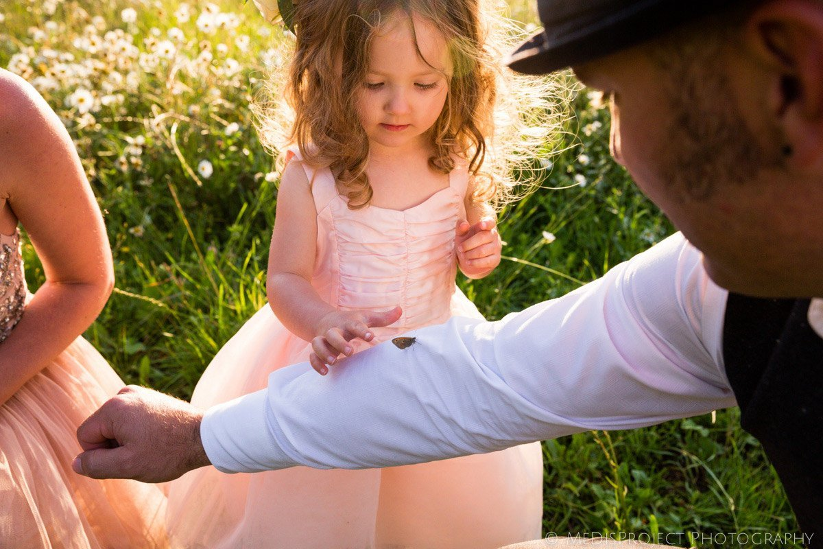 little flower girl palying with a butterfly on her father's sleeves