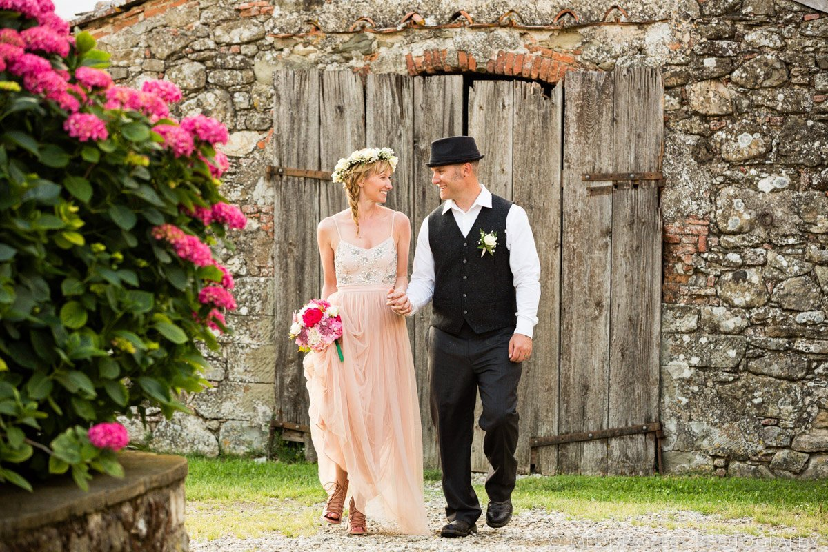 just married couple among flowers and country stone walls