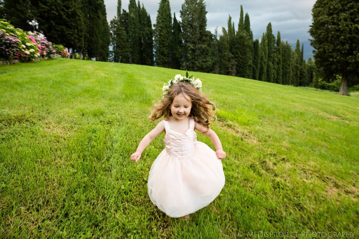 little flower girl running in a villa garden