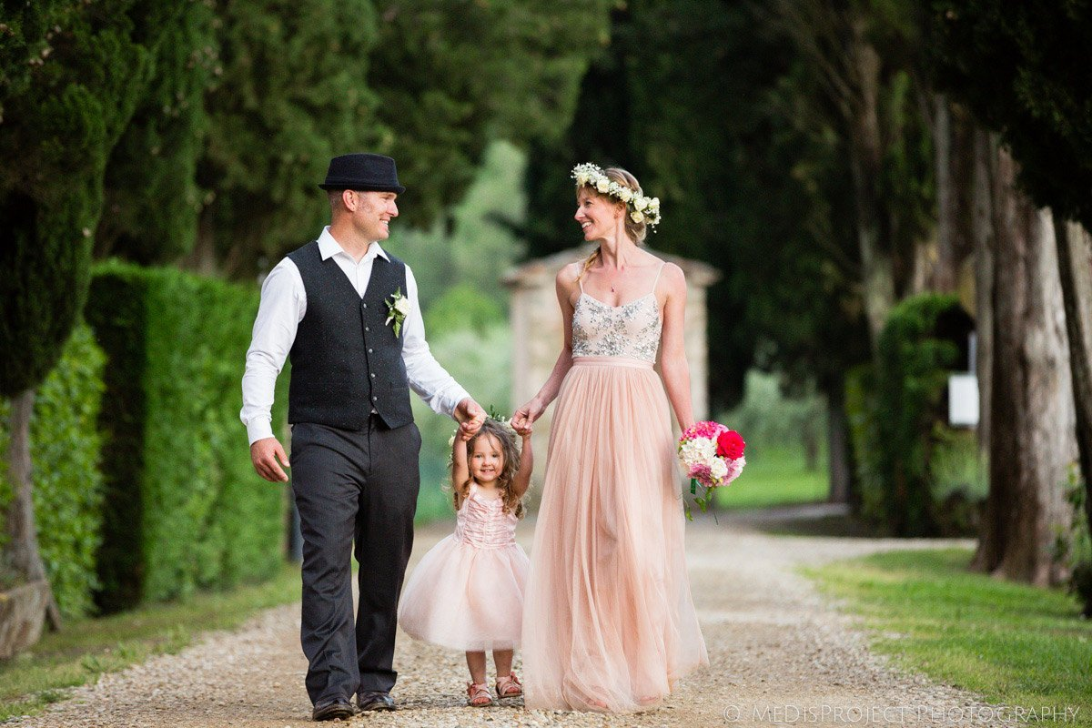 just married couple walking hand by hand with their baby daughter